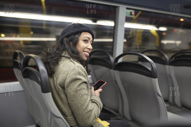 Smiling woman sitting in a public bus at night