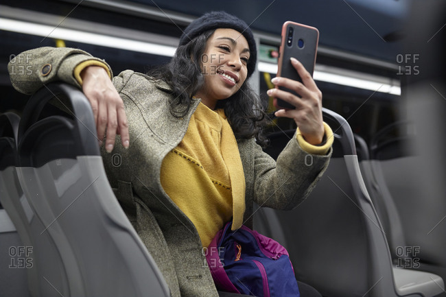 Woman sitting and using his cellphone in a public bus at night