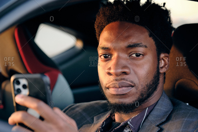 African American business man checking phone in sports car at sunset