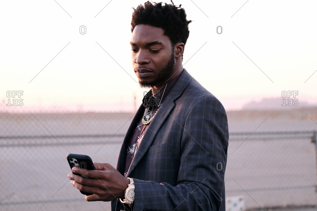 African American business man checking phone at sunset
