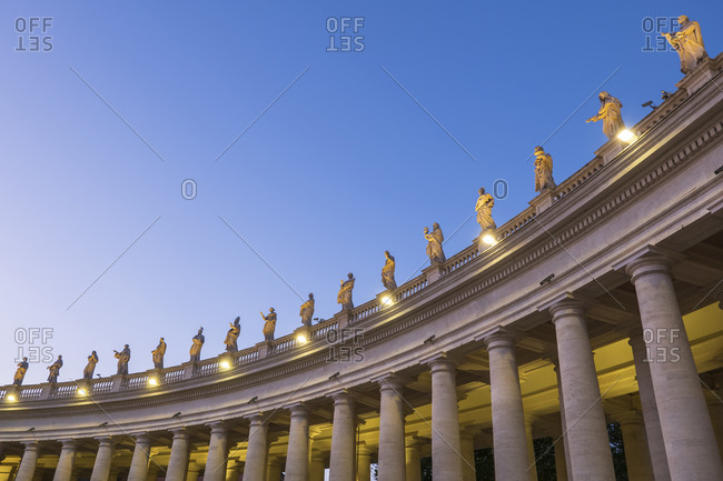 September 5, 2020: Illuminated saint statues on St. Peter's Basilica against clear blue sky at dusk- Vatican City- Rome- Italy
