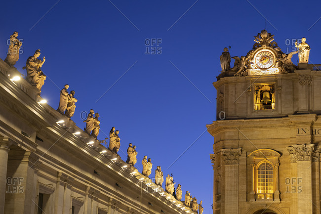September 5, 2020: Illuminated saint statues on St. Peter's Basilica against clear blue sky at night- Vatican City- Rome- Italy