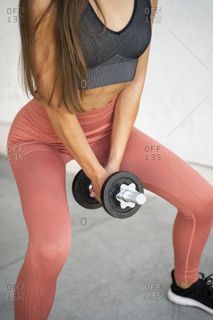 Female athlete lifting dumbbell while exercising outdoors