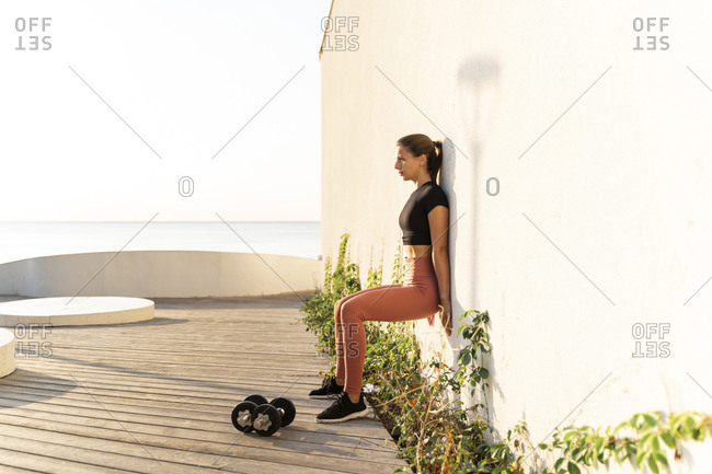Sportswoman doing wall sit exercise while leaning on wall