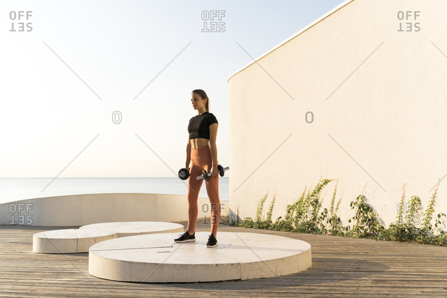 Young female athlete lifting dumbbell exercising on pedestal by sea during sunrise