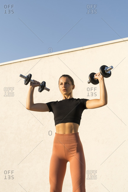 Female athlete flexing muscles with dumbbell standing against wall during sunrise
