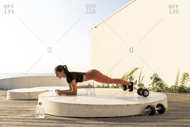 Sportswoman doing plank position exercise on pedestal by sea during sunrise