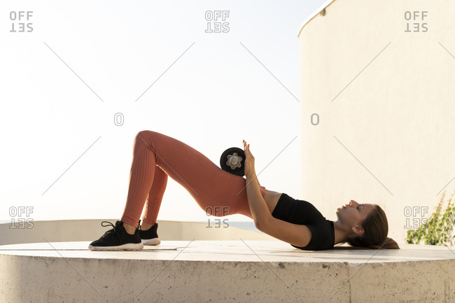 Female athlete doing bridge position exercise on pedestal during sunrise