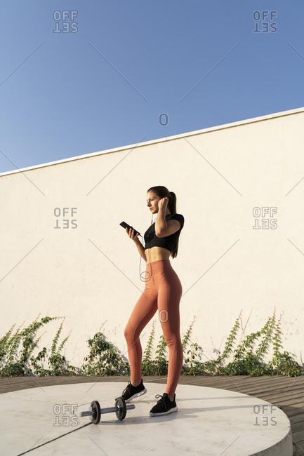 Female athlete using smart phone listening music through earphone standing on pedestal during sunrise