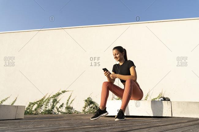 Smiling female athlete using smart phone listening music through earphone sitting on pedestal during sunrise