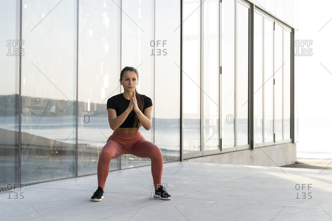 Young sportswoman doing squat exercise on promenade against glass window