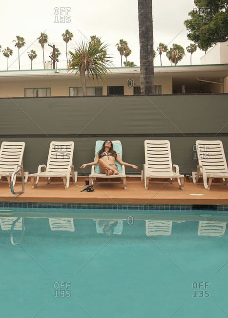 Woman relaxing on deck chair at poolside during summer vacation