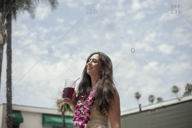 Young woman standing with juice drink wearing floral garland against cloudy sky