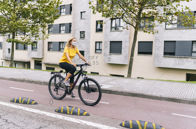 Mature woman cycling on bicycle lane in city during COVID-19