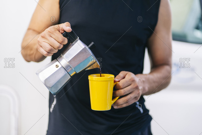 Mid adult man pouring coffee from coffee pot into coffee cup while standing at home