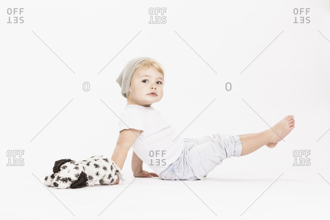 Cute little girl playing with stuffed toy in studio