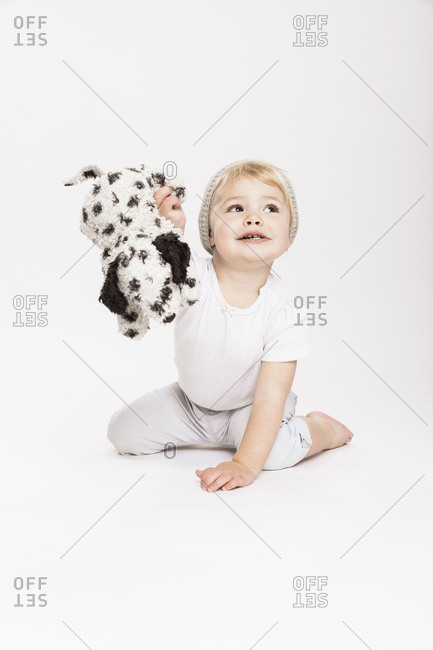 Female toddler holding stuffed toy while sitting in studio against white background