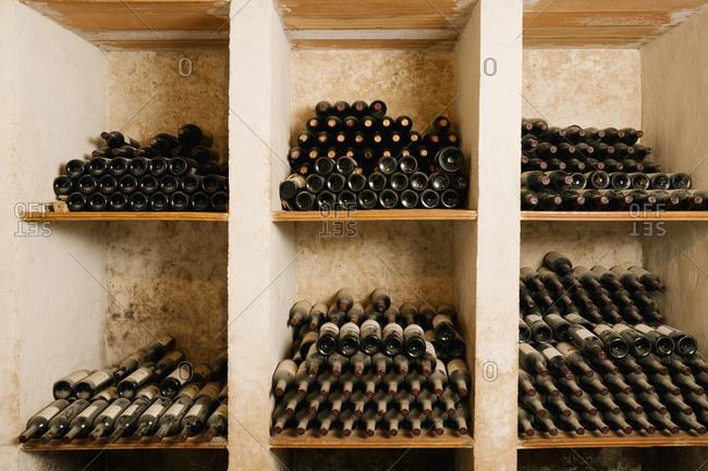 Stack of old wine bottles in rack at cellar