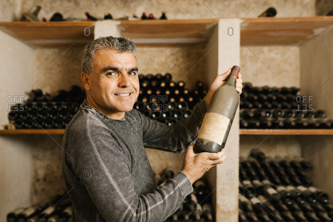 Smiling male owner holding old wine bottle while standing by rack at cellar