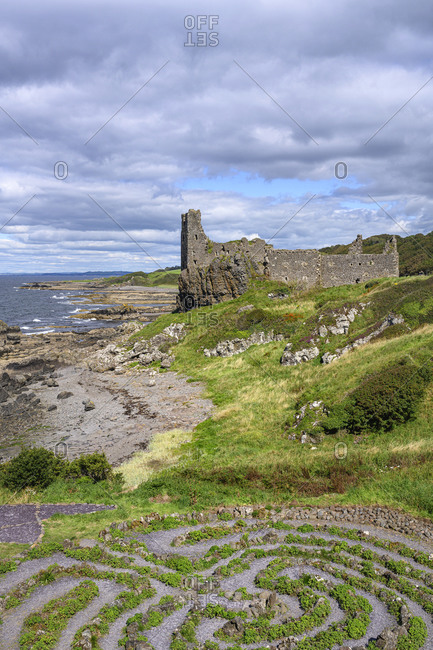 UK- Scotland- Abandoned garden with ruins of Dunure Castle in background