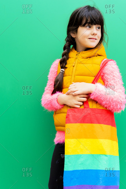 Girl carrying colorful bag looking away while standing against green wall