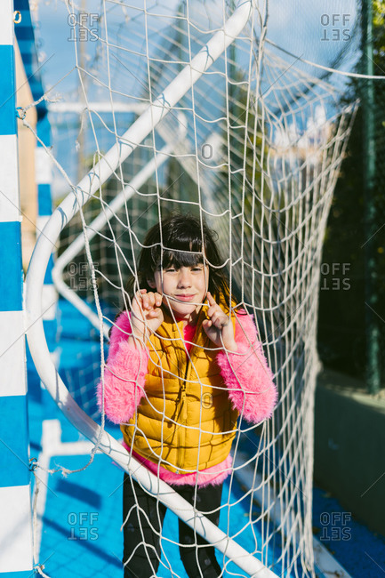 Cute girl leaning on goal post net at soccer court during sunny day