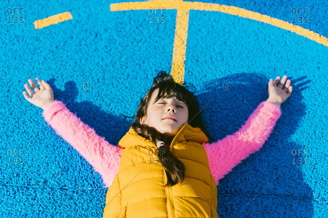 Girl relaxing with arms raised on basketball court