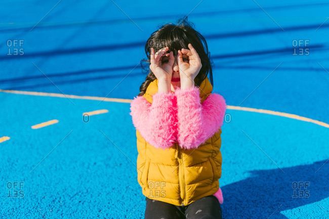Girl forming binoculars with fingers while sitting at sports court