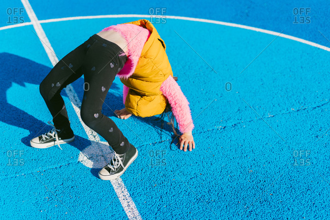 Girl doing acrobatic activity on soccer court during sunny day