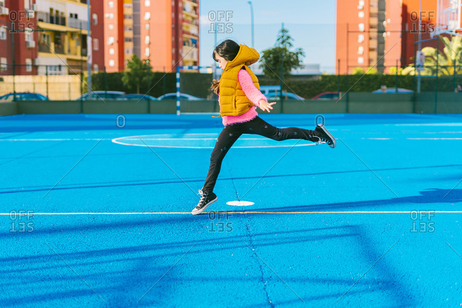 Girl jumping on blue sports court during sunny day