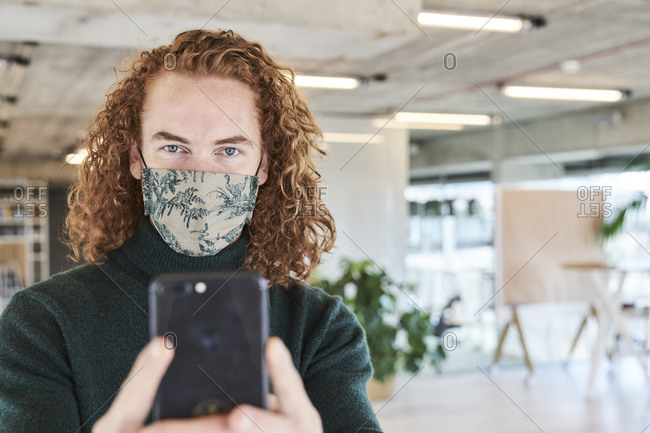 Man in protective face mask photographing through mobile phone in studio apartment