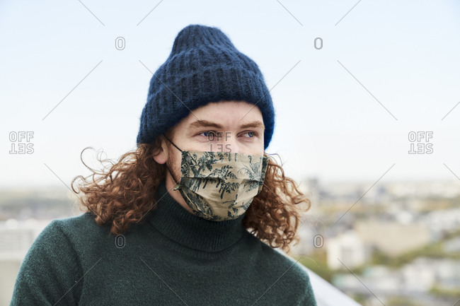 Thoughtful man with curly long hair wearing protective face mask and beanie on rooftop