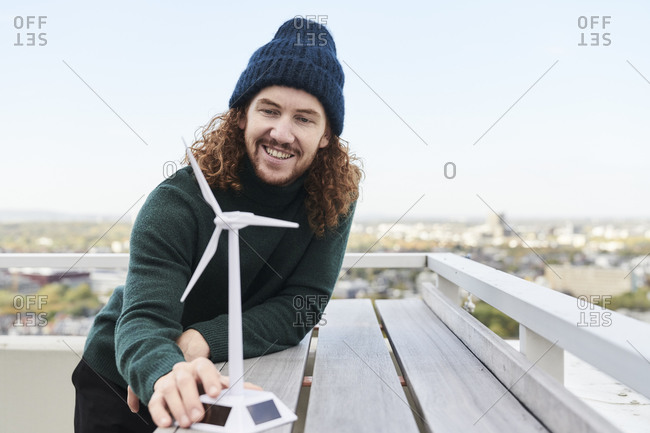 Smiling male hipster with windmill model on building terrace against sky