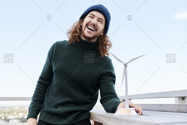Cheerful man with windmill model on building terrace against sky