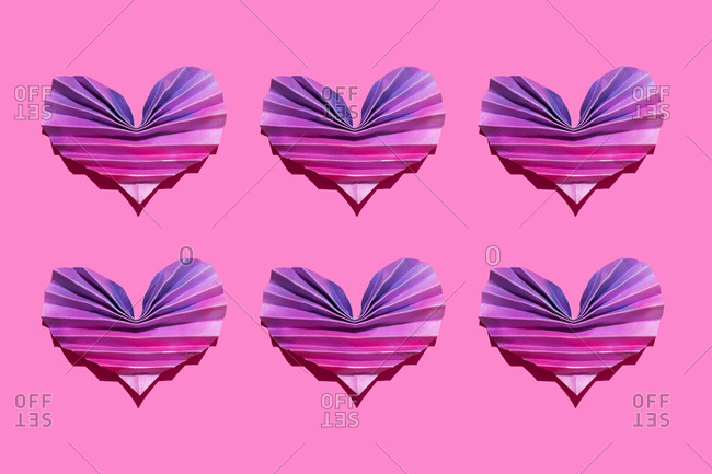 Studio shot of six pink and purple origami hearts
