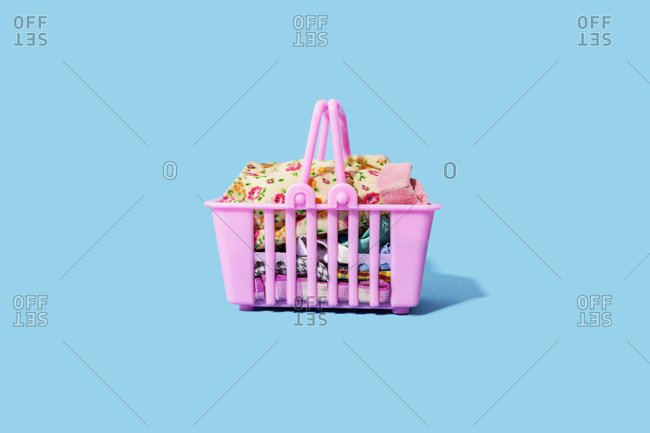 Studio shot of pink shopping basket filled with clothing