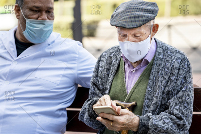Senior man using smart phone wearing protective face mask sitting with mature male on bench during COVID-19