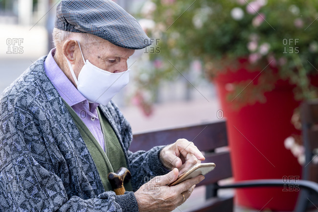 Active senior man using smart phone sitting on bench outdoors