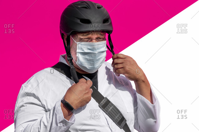 Doctor with face mask and bag wearing cycling helmet while standing against multicolored wall