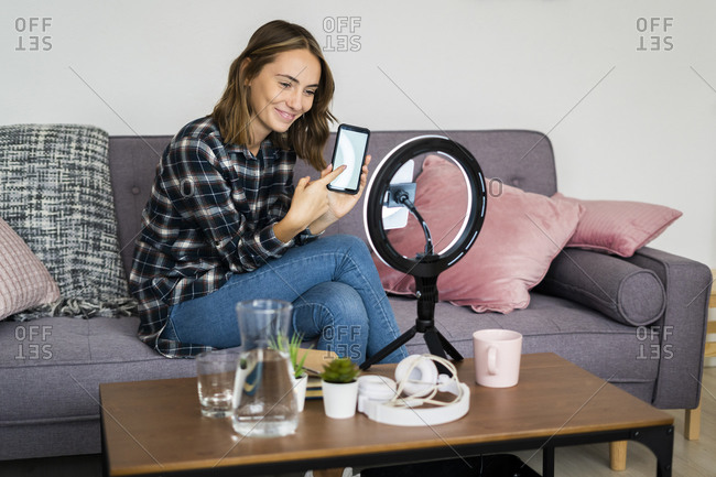 Young woman showing mobile phone attached to ring flash while live streaming at home