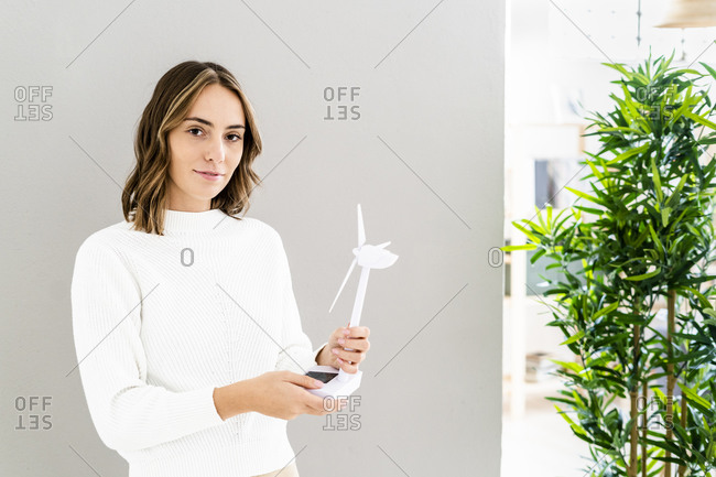 Businesswoman holding wind turbine toy while standing at office