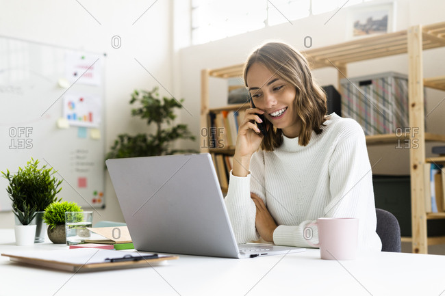 Smiling businesswoman talking on mobile phone while working on laptop at office