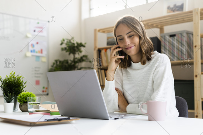 Businesswoman talking on mobile phone while working on laptop at office