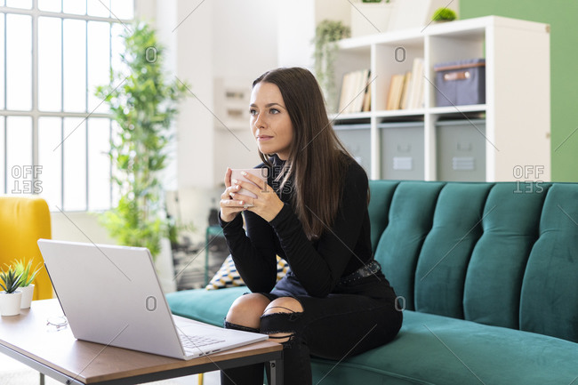 Thoughtful young woman holding coffee cup while sitting with laptop on sofa in loft apartment