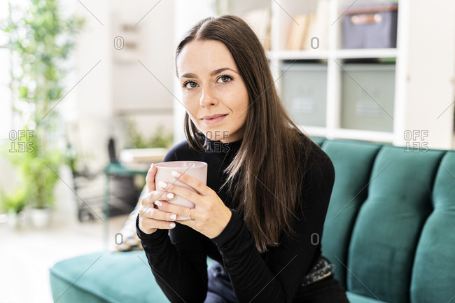 Beautiful young woman holding coffee cup while sitting on sofa in living room at home