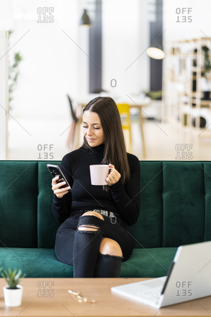 Young female influencer holding smart phone and coffee cup while sitting on sofa at loft apartment