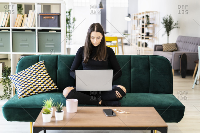 Beautiful young woman using laptop for blogging while sitting on sofa at loft apartment