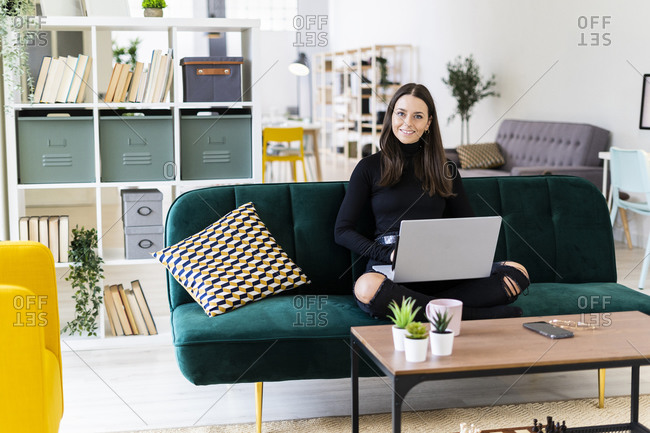 Young female blogger sitting with laptop on sofa at loft apartment