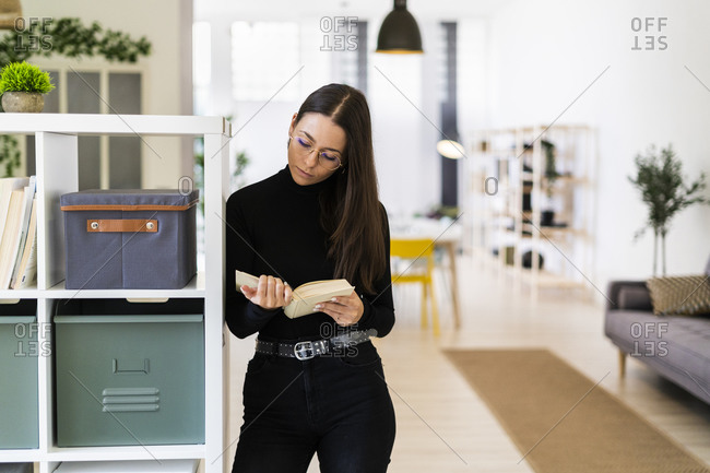 Beautiful young woman reading book while standing by rack at home
