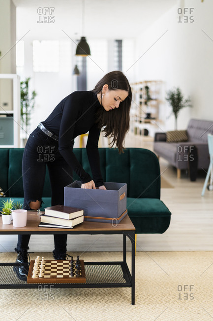 Young woman collecting books in box on coffee table at loft apartment